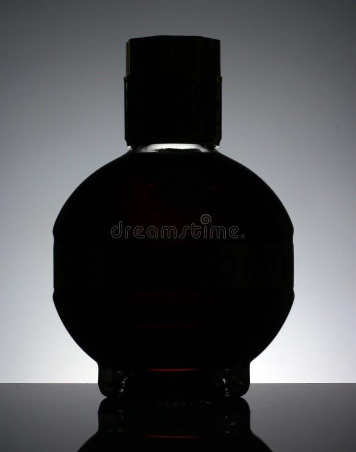 Μπουκάλι ηδύποτου σε έναν μαύρο πίνακα με το γκρίζο υπόβαθρο στοκ εικόνες