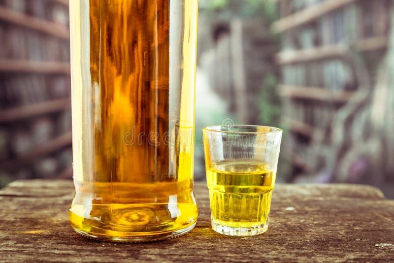 Μπουκάλι και γυαλί που πυροβολούνται με το κίτρινο liqour στοκ εικόνα