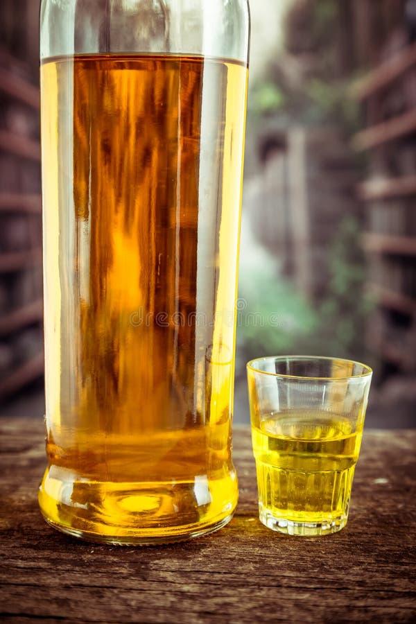 Μπουκάλι και γυαλί που πυροβολούνται με το κίτρινο liqour στοκ φωτογραφίες