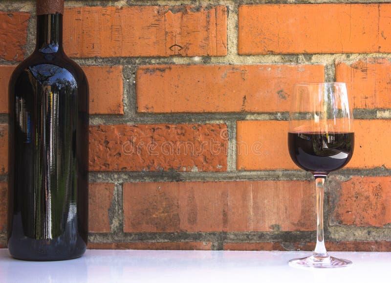 Μπουκάλι και ποτήρι του κόκκινου κρασιού κοντά στον τοίχο των πορτοκαλιών τούβλων σοφίτα ST στοκ φωτογραφίες