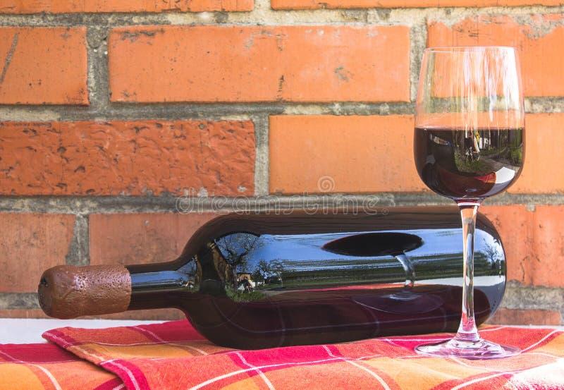 Μπουκάλι και ποτήρι του κόκκινου κρασιού κοντά στον τοίχο των πορτοκαλιών τούβλων σοφίτα ST στοκ εικόνα
