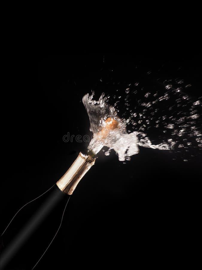 Μπουκάλι και ψεκασμός CHAMPAGNE στο μαύρο backgroun στοκ εικόνα με δικαίωμα ελεύθερης χρήσης