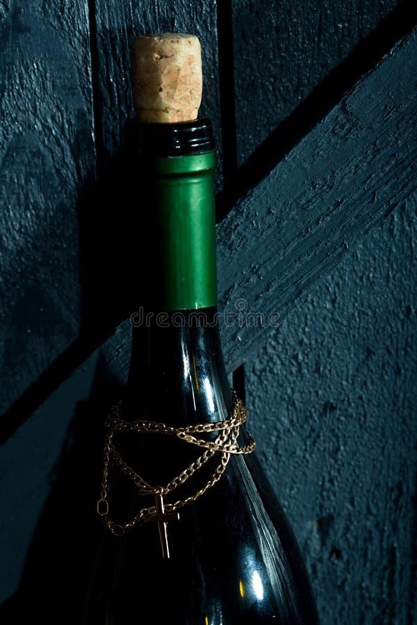 Μπουκάλι με τη χρυσούς αλυσίδα και το σταυρό στοκ φωτογραφίες