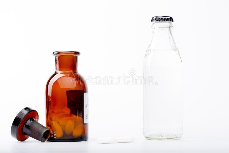 Μπουκάλι νερό, ένα μπουκάλι ιατρικής γυαλιού και ένα λευκό στοκ φωτογραφία