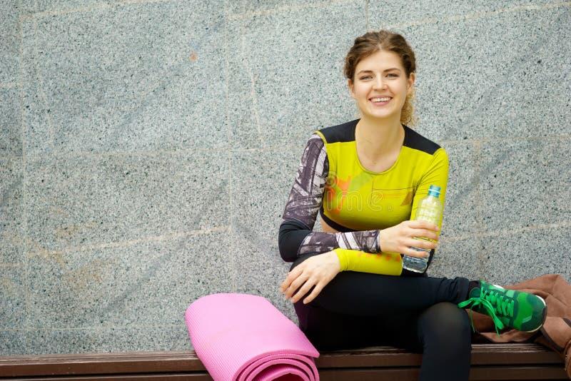 Μπουκάλι νερό χαμογελώντας γυναικών συνεδρίασης σχεδόν χαλιών και εκμετάλλευσης στοκ εικόνες