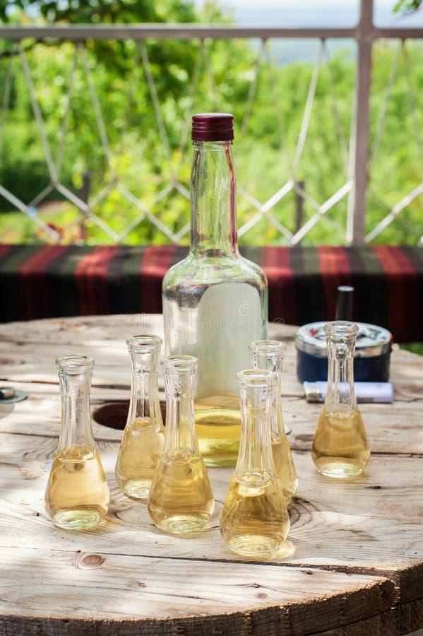 Μπουκάλι του κονιάκ δαμάσκηνων με τα μικρά γυαλιά στον ξύλινο πίνακα στοκ φωτογραφία με δικαίωμα ελεύθερης χρήσης