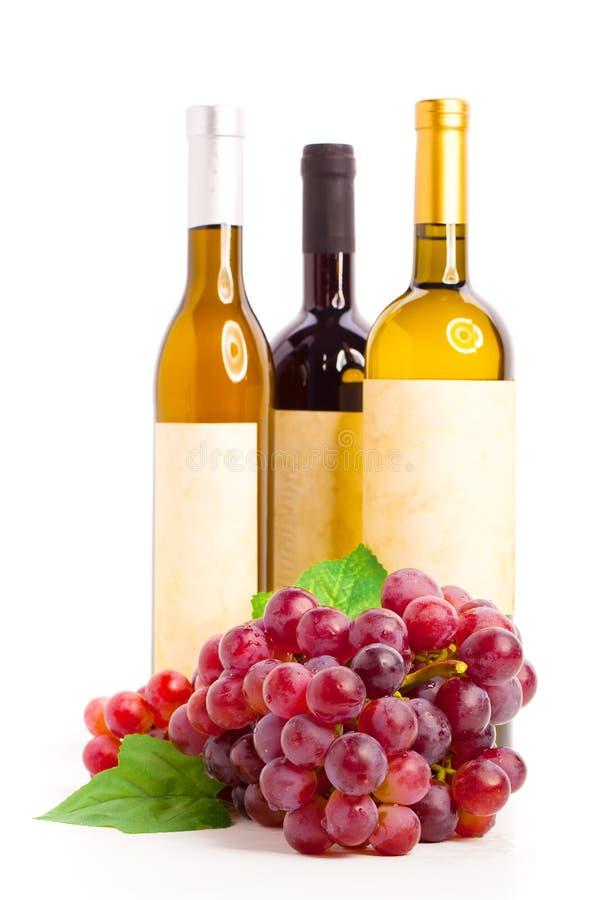 Μπουκάλι του κόκκινου και άσπρου κρασιού με τα σταφύλια, στοκ φωτογραφία