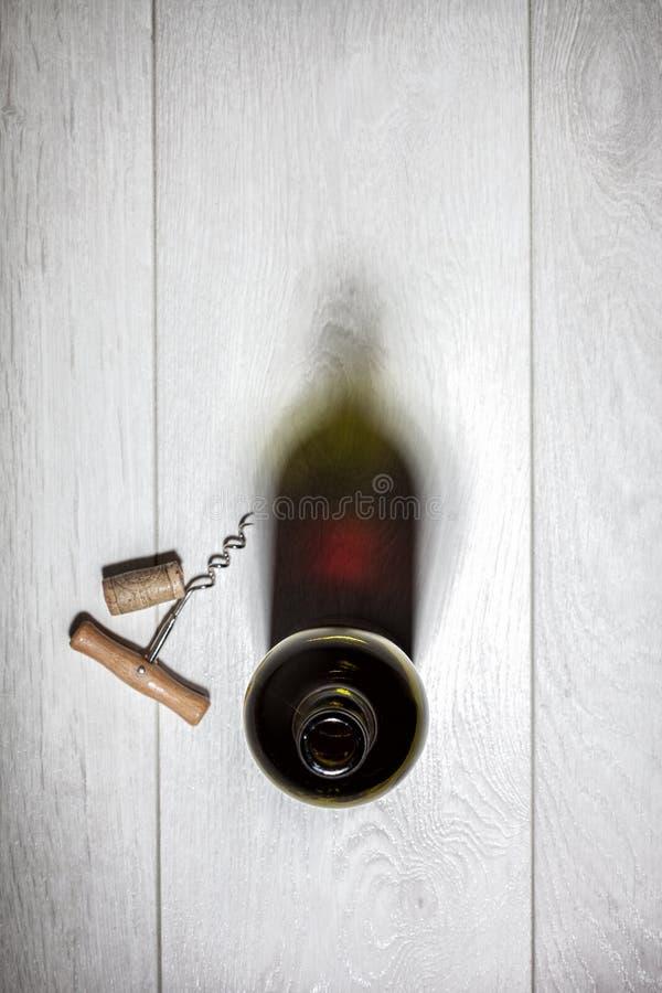 Μπουκάλι του κόκκινου κρασιού με το φελλό στον άσπρο ξύλινο πίνακα στοκ εικόνα