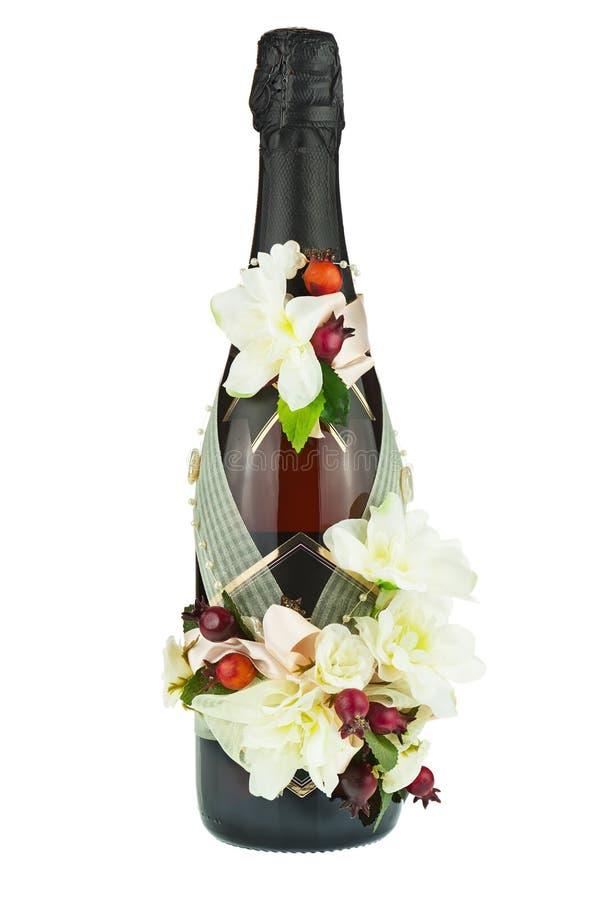 Μπουκάλι CHAMPAGNE με τη γαμήλια διακόσμηση των ρυθμίσεων λουλουδιών στοκ φωτογραφία