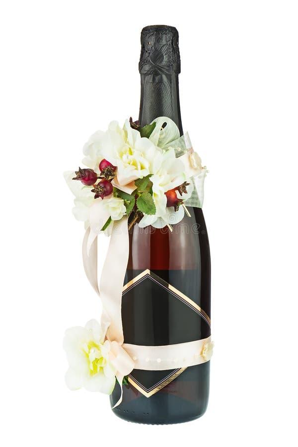 Μπουκάλι CHAMPAGNE με τη γαμήλια διακόσμηση των ρυθμίσεων λουλουδιών στοκ φωτογραφίες