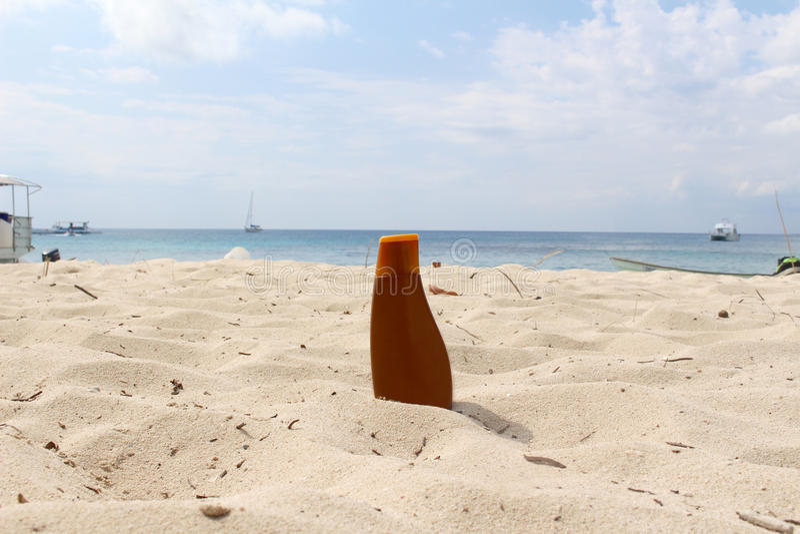 Μπουκάλι Sunblock στην παραλία στοκ φωτογραφία