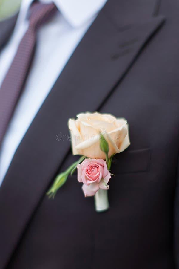 Μπουτονιέρα στο γαμήλιο σακάκι νεόνυμφων ` s στοκ φωτογραφία με δικαίωμα ελεύθερης χρήσης