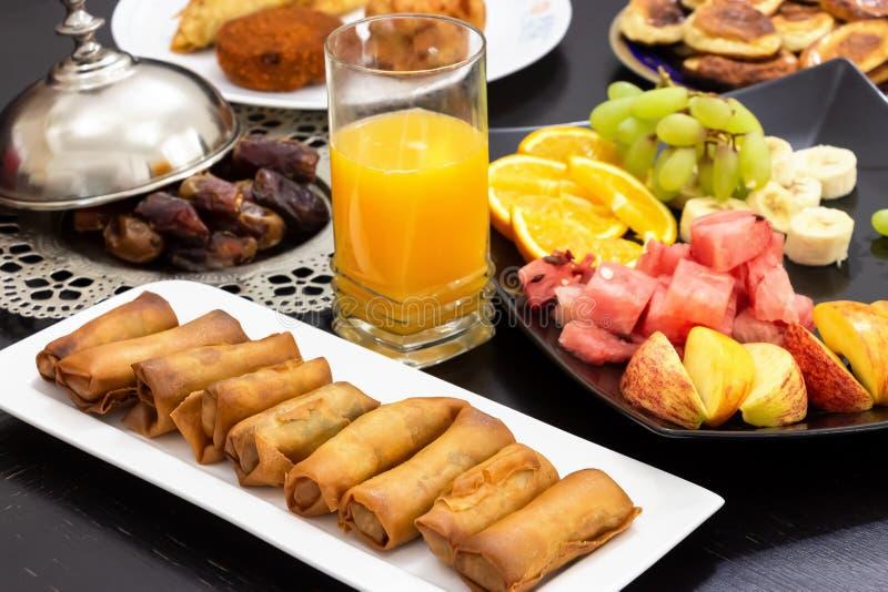 Μπουφές Iftar Ρόλος άνοιξη, φρούτα, φρέσκος χυμός από πορτοκάλι, πρόχειρο φαγητό samosa, ρόλος άνοιξη και iftar ιερός μήνας έννοι στοκ φωτογραφία