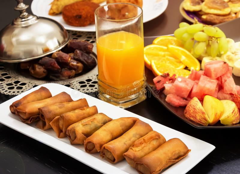 Μπουφές Iftar Ρόλος άνοιξη, φρούτα, φρέσκος χυμός από πορτοκάλι, πρόχειρο φαγητό samosa, ρόλος άνοιξη και iftar ιερός μήνας έννοι στοκ φωτογραφίες