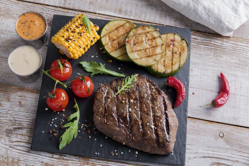 Μπριζόλα βόειου κρέατος με τα ψημένα στη σχάρα λαχανικά σε μια επιφάνεια πετρών στοκ φωτογραφίες