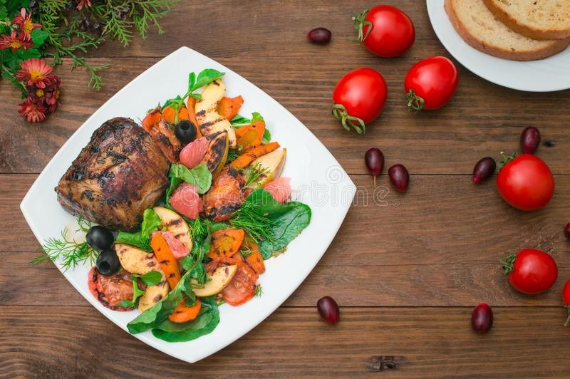 Μπριζόλα βόειου κρέατος με τα ψημένα στη σχάρα λαχανικά, το σπανάκι και το γκρέιπφρουτ με τα μήλα αγροτικός ξύλινος ανασκόπησης Τ στοκ εικόνες
