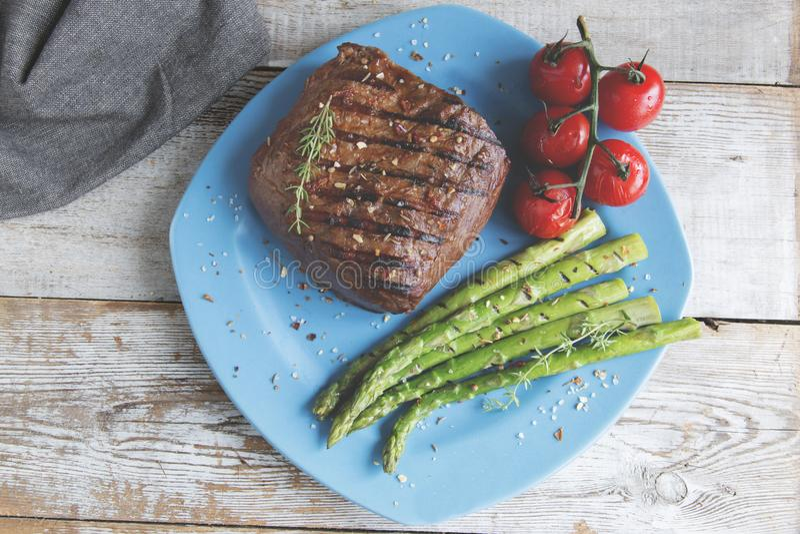 Μπριζόλα βόειου κρέατος που ψήνεται στη σχάρα με τις ντομάτες σπαραγγιού σε ένα πιάτο στοκ εικόνες με δικαίωμα ελεύθερης χρήσης