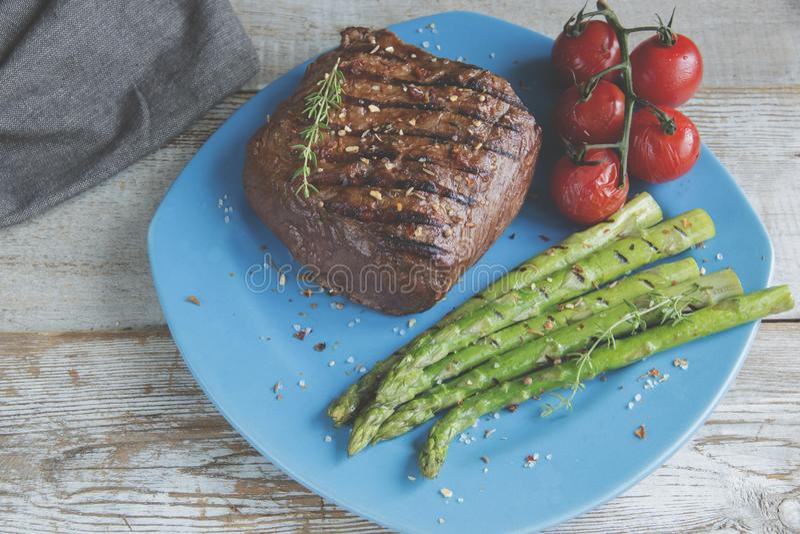 Μπριζόλα βόειου κρέατος που ψήνεται στη σχάρα με το καρύκευμα ντοματών σπαραγγιού στο πιάτο στοκ φωτογραφίες