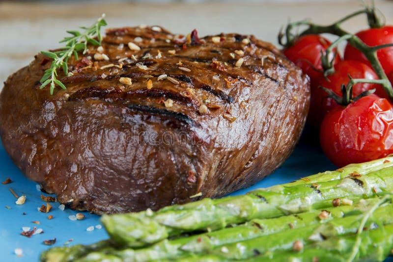 Μπριζόλα βόειου κρέατος που ψήνεται στη σχάρα με το σπαράγγι, ντομάτες, καρύκευμα στοκ φωτογραφία