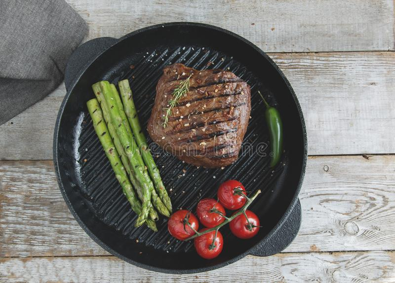 Μπριζόλα βόειου κρέατος που ψήνεται στη σχάρα στο τηγανίζοντας τηγάνι με το καρύκευμα ντοματών σπαραγγιού στοκ εικόνα με δικαίωμα ελεύθερης χρήσης