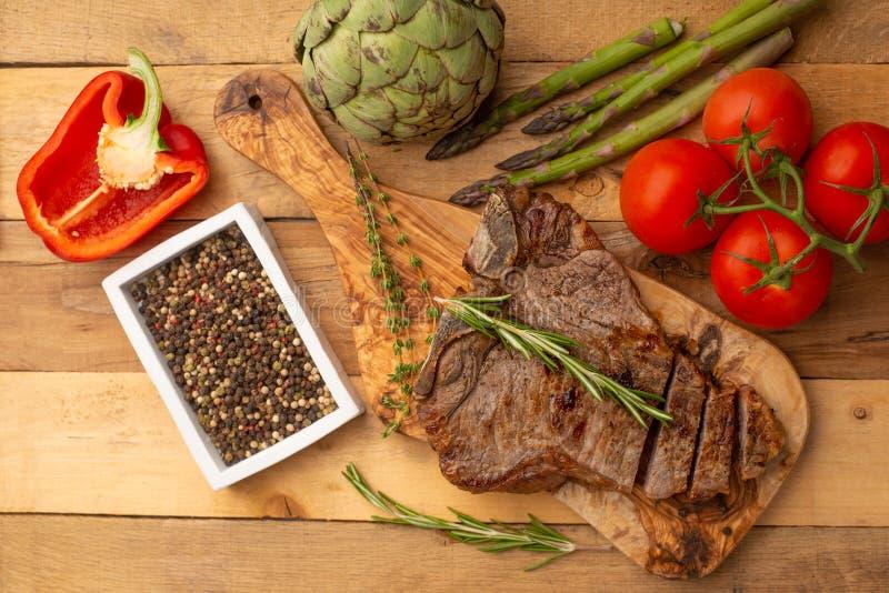 Μπριζόλα βόειου κρέατος σε έναν πίνακα με το πιπέρι δεντρολιβάνου, το καρύκευμα, και τα φρέσκα λαχανικά, τις ντομάτες και το σπαρ στοκ φωτογραφίες