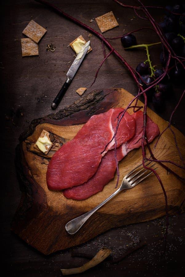 Μπριζόλα βόειου κρέατος, συστατικά φρέσκου κρέατος για το μαγείρεμα στον πίνακα κουζινών στοκ εικόνα