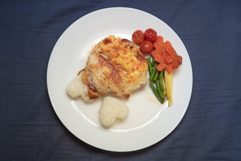 Μπριζόλα κοτόπουλου με τις ντομάτες, τα καρότα, τα δημητριακά, τα φασόλια και το ρύζι στοκ φωτογραφία