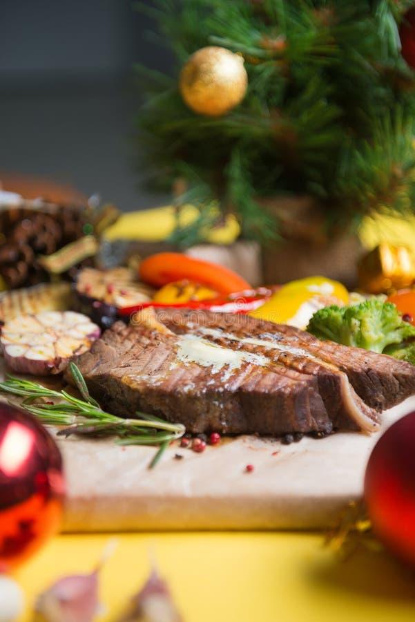 Μπριζόλα κρέατος με τα λαχανικά κομψοί κλάδοι και σφαίρες Χριστουγέννων στο σκηνικό στοκ εικόνες