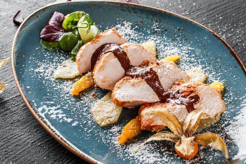 Μπριζόλα κρέατος της Τουρκίας με την καραμελοποιημένη σάλτσα τσίλι φρούτων και σοκολάτας στο πιάτο στο σκοτεινό υπόβαθρο πετρών Κ στοκ εικόνες