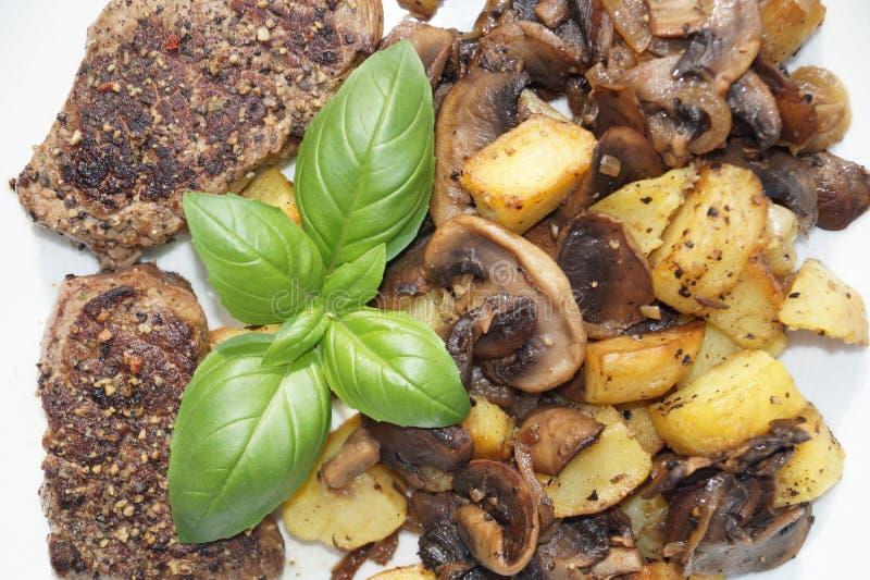 Μπριζόλα με το ψημένες μανιτάρι, τα κρεμμύδια και τις πατάτες στοκ φωτογραφίες