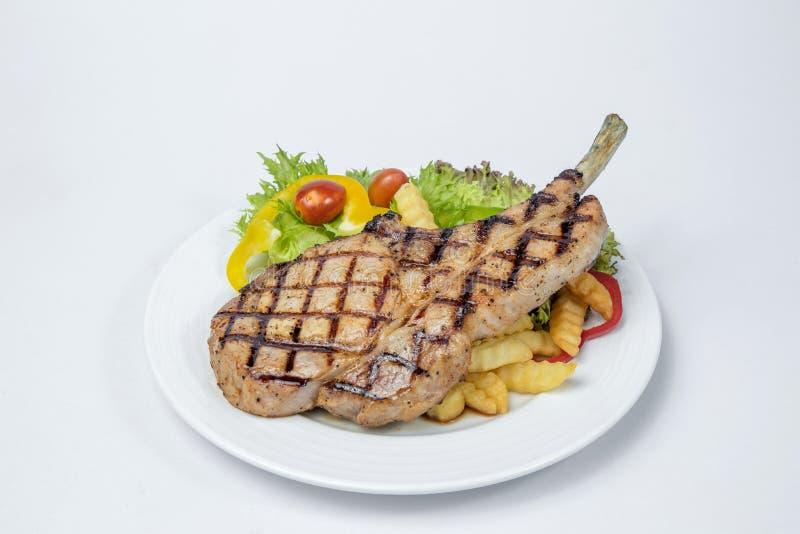 Μπριζόλα μπριζολών χοιρινού κρέατος που εξυπηρετούνται με τη φρέσκια σαλάτα και γαλλικά που τηγανίζεται στοκ φωτογραφία με δικαίωμα ελεύθερης χρήσης