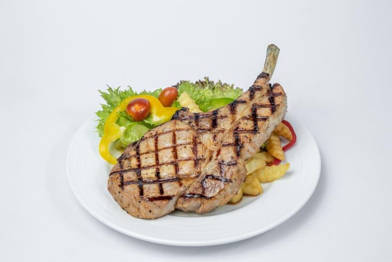 Μπριζόλα μπριζολών χοιρινού κρέατος που εξυπηρετούνται με τη φρέσκια σαλάτα και γαλλικά που τηγανίζεται στοκ εικόνα