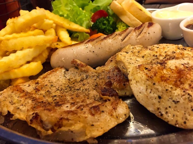 Μπριζόλα που αναμιγνύεται σαλάτα με τη σάλτσα ζωμού, υπάρχει ψημένο στη σχάρα κοτόπουλο, μπριζόλα χοιρινού κρέατος με το μαύρο πι στοκ εικόνα