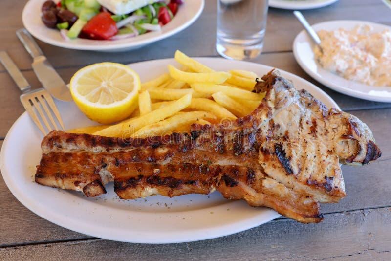 Μπριζόλα χοιρινού κρέατος με τη μερίδα τηγανιτών πατατών στην ελληνική ταβέρνα στοκ φωτογραφία με δικαίωμα ελεύθερης χρήσης