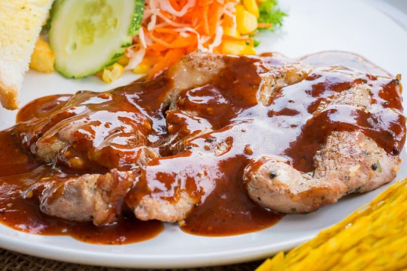 Μπριζόλα βόειου κρέατος με τη μαύρη σάλτσα, τη σαλάτα και τις τηγανιτές πατάτες πιπεριών στο s στοκ φωτογραφία με δικαίωμα ελεύθερης χρήσης