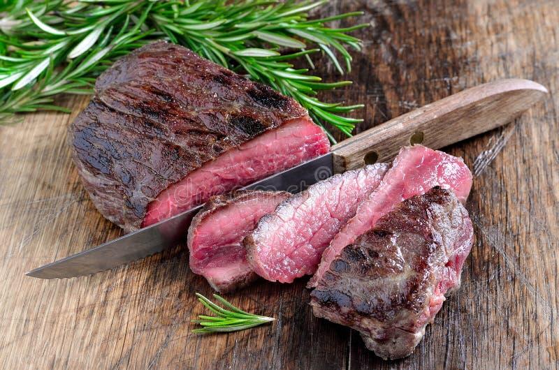 Μπριζόλα βόειου κρέατος που κόβεται με ένα μαχαίρι στοκ εικόνα