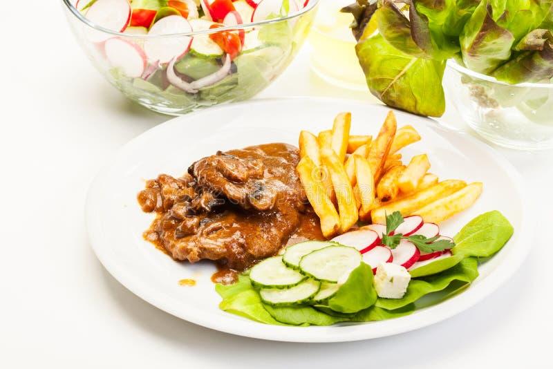 Μπριζόλα χοιρινού κρέατος με τη σάλτσα, τα μανιτάρια και τα τσιπ στοκ εικόνες