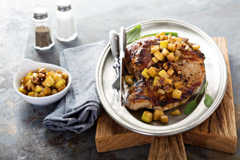 Μπριζόλες χοιρινού κρέατος με τα μήλα και τα ξύλα καρυδιάς στοκ φωτογραφία