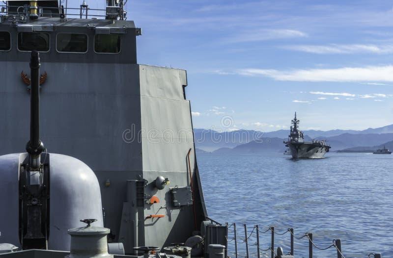 Μπροστινά ταϊλανδικά σκάφος παράκτιας περιπόλου HTMS Narathiwat και JS Ise πίσω από το ιαπωνικό πανί καταστροφέων ελικοπτέρων στη στοκ φωτογραφία