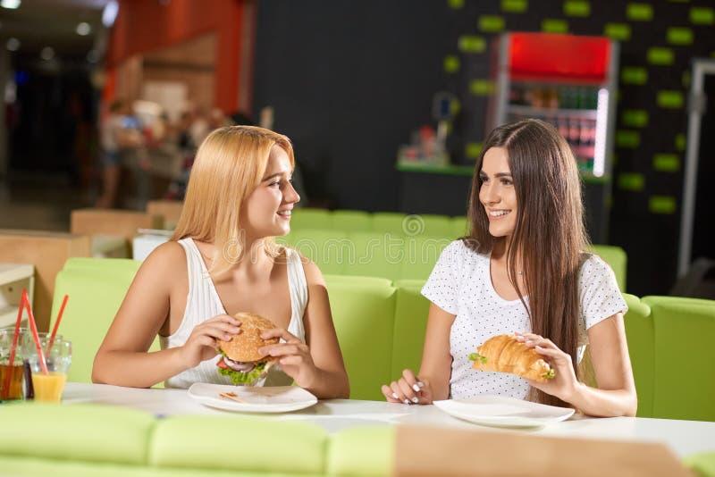 Μπροστινή άποψη δύο κοριτσιών που τρώνε burger και croissant στον καφέ στοκ φωτογραφία με δικαίωμα ελεύθερης χρήσης