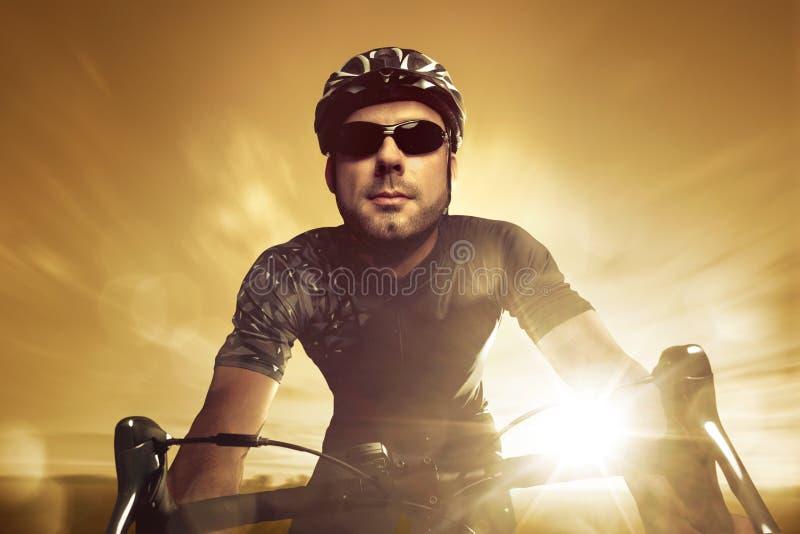 Μπροστινή άποψη ενός επαγγελματικού ποδηλάτη κατά τη διάρκεια του ηλιοβασιλέματος στοκ εικόνες