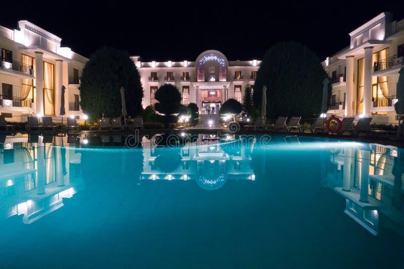 Μπροστινή άποψη ξενοδοχείων πολυτελείας με τη μεγάλη λίμνη, τη νύχτα στοκ εικόνες