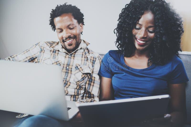 Μπροστινή άποψη της ευτυχούς χαλάρωσης ζευγών αφροαμερικάνων μαζί στον καναπέ Νέος μαύρος και η χρησιμοποίηση φίλων του στοκ εικόνα με δικαίωμα ελεύθερης χρήσης