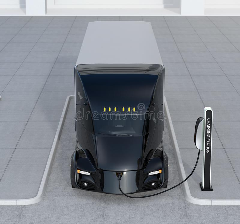 Μπροστινή άποψη της μόνος-οδήγησης του ηλεκτρικού φορτηγού που χρεώνει στο σταθμό χρέωσης στοκ εικόνες