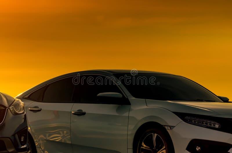 Μπροστινή άποψη του άσπρου αυτοκινήτου με την πολυτέλεια και το σύγχρονο σχέδιο που σταθμεύουν στο χώρο στάθμευσης με τον όμορφο  στοκ φωτογραφία με δικαίωμα ελεύθερης χρήσης