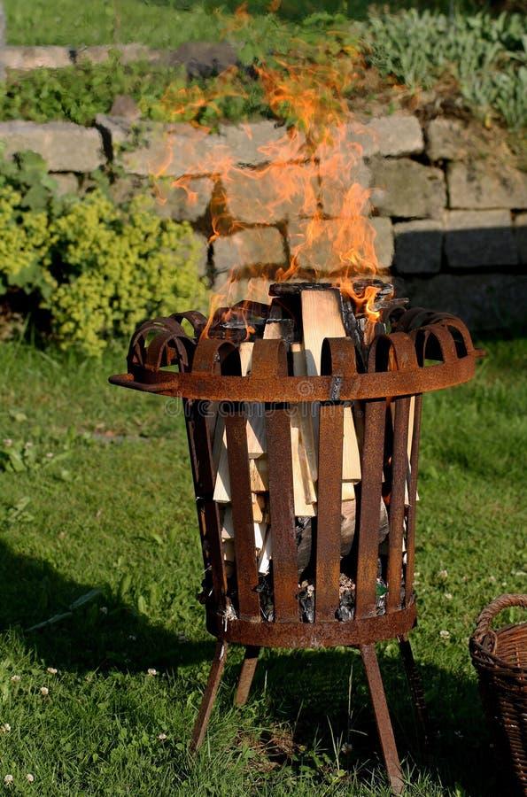Μπροστινή άποψη του καψίματος του παλαιού σκουριασμένου καλαθιού πυρκαγιάς στον κήπο στοκ φωτογραφίες
