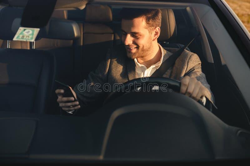 Μπροστινή άποψη του χαμόγελου bussinesman στο κοστούμι που οδηγεί το αυτοκίνητό του στοκ εικόνες