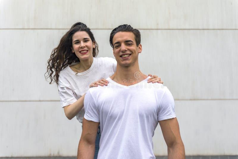 Μπροστινή άποψη του όμορφου νέου ζεύγους που αγκαλιάζει, που εξετάζει τη κάμερα και που χαμογελά στεμένος υπαίθρια στοκ εικόνες με δικαίωμα ελεύθερης χρήσης