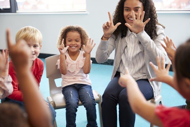 Μπροστινή άποψη των παιδιών σχολείου νηπίων που κάθονται στις καρέκλες σε έναν κύκλο στην τάξη, που κρατά ψηλά τα χέρια τους και  στοκ φωτογραφίες