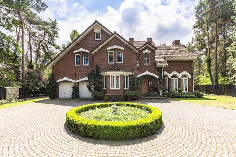 Μπροστινή άποψη driveway με έναν στρογγυλό κήπο και ένα μεγάλο, αγγλικό ST στοκ εικόνες με δικαίωμα ελεύθερης χρήσης